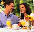Photo of a happy couple sitting at breakfast outside on a deck in Niagara